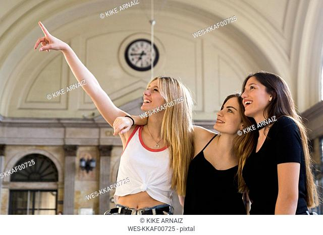 Three young women watching something at concourse