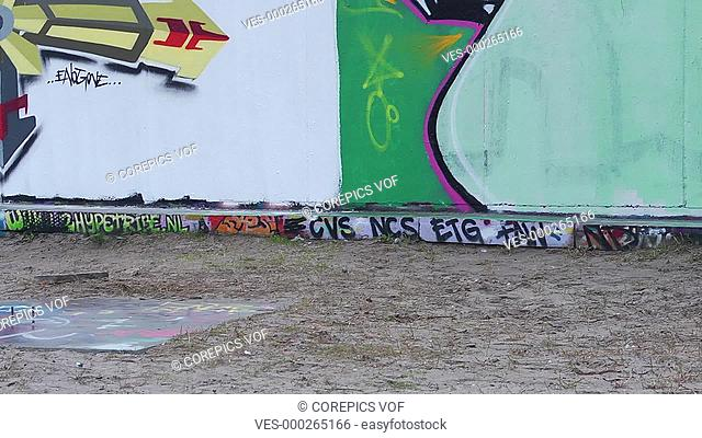 Pan over a graffiti clad wall, past a couch, with the graffiti artist relaxing after finishing his artwork