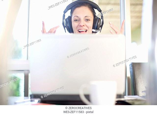 Happy woman at desk with laptop and headset