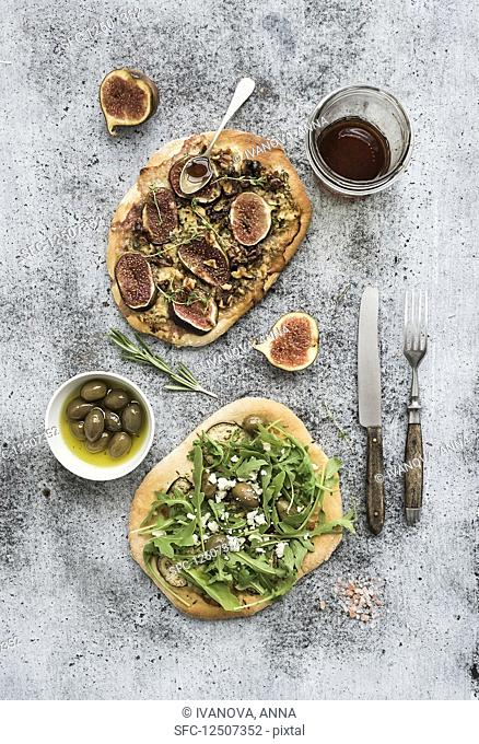 Rustic homemade pizzas with eggpant, cheese, olives, arugula, prosciutto and figs over grunge backdrop