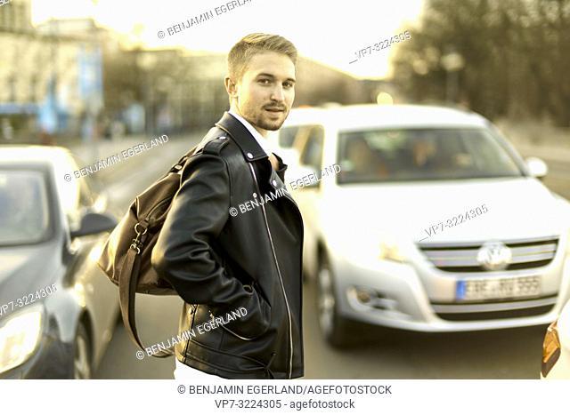 man crossing street between cars, city, Munich, Germany