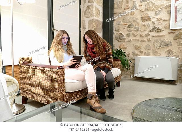 girls watching an ebook in the living room, Madrid, Spain