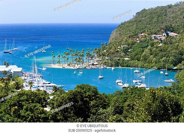 Marigot Bay The harbour with yachts at anchor the and lush surrounding valley. The small coconut palm tree lined beach of the Marigot Beach Club sits at the...