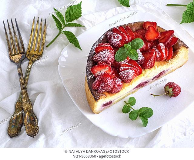 Cheesecake of cottage cheese and fresh strawberries on a white ceramic plate, next to two forks, top view