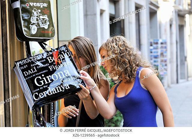 Two girls looking at a bag in a tourist shop, Girona, Catalonia, Spain, Europe