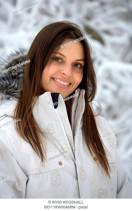 Female by snow covered trees