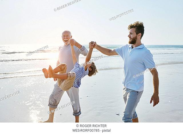 Happy grandfather, father and son on the beach