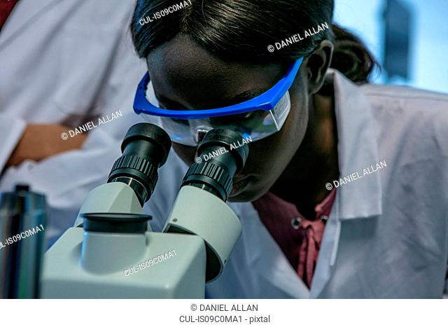 Young female scientist looking through microscope in laboratory, close up