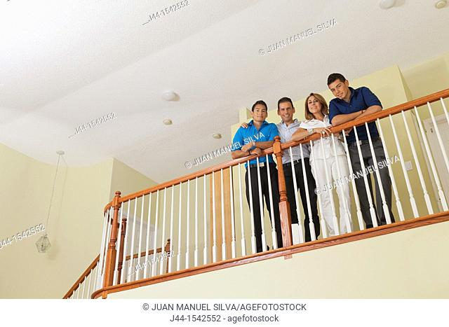 Portrait of Hispanic family standing by railing in house