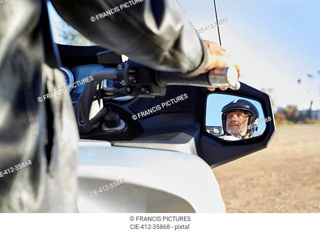 View of senior man in side-view mirror riding motorcycle