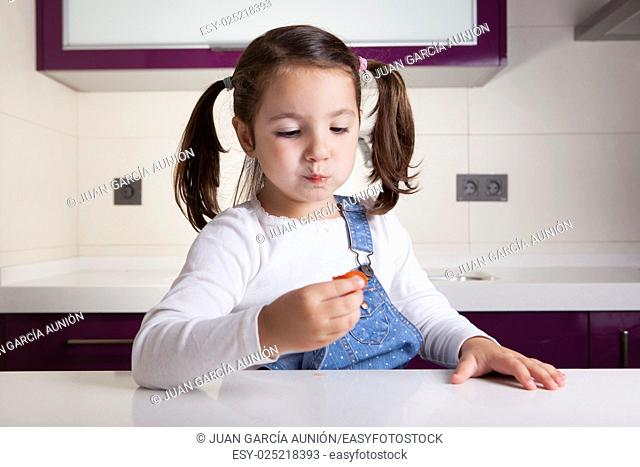 Little girl tasting a raw colorful cherry tomatoe