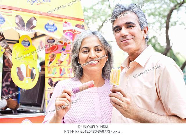 Mature couple eating ice cream candies, Lodi Gardens, New Delhi, India