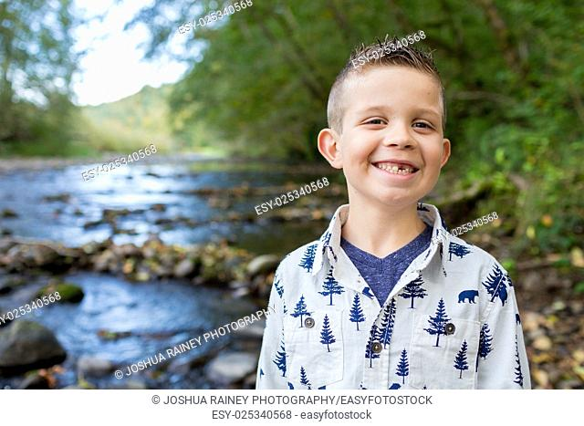 Young boy posing for a lifestyle portrait outdoors along the banks of the McKenzie River in Oregon