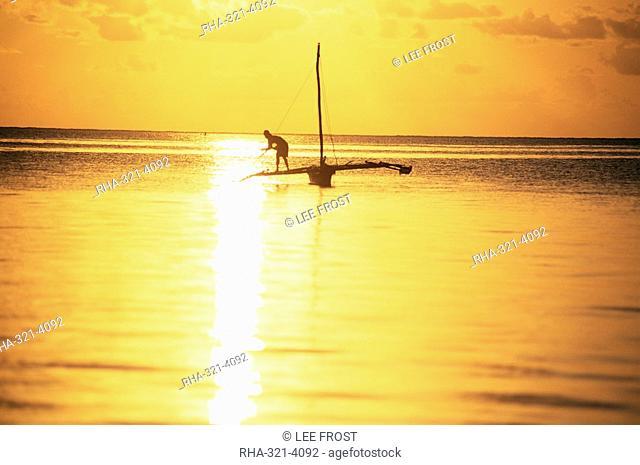 Outrigger canoe and fisherman in silhouette at sunrise off Jambiani, Zanzibar, Tanzania, East Africa, Africa