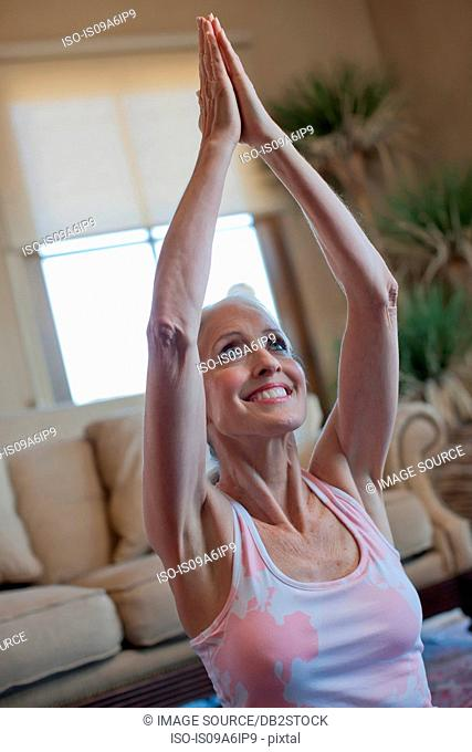 Older woman practicing yoga at home