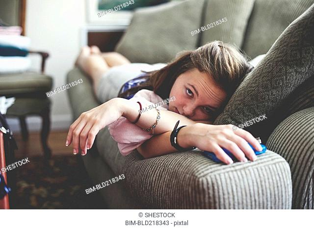 Close up of girl laying on sofa in living room
