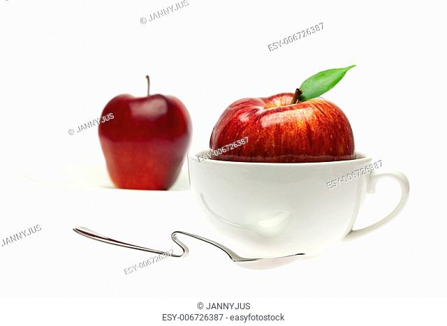 apple in a cup and spoon isolated on white