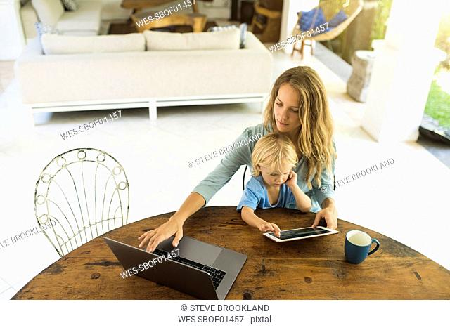 Boy sitting on his mother's lap and looking at a tablet while his mother is working on a laptop