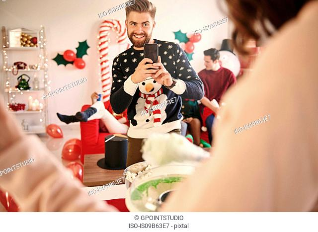 Young man photographing woman preparing candyfloss at christmas party