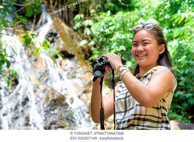 Beautiful young girl hiking is using binoculars look for birds smiling to the camera in tropical forest near the waterfalls in Thailand