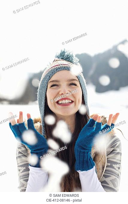Happy woman watching snow fall