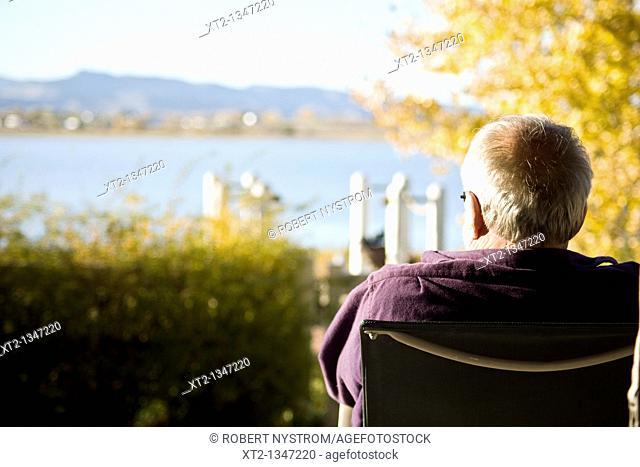 An elderly man sitting in a chair looking out at a lake and mountains in colorado during the fall season with yellow leaves