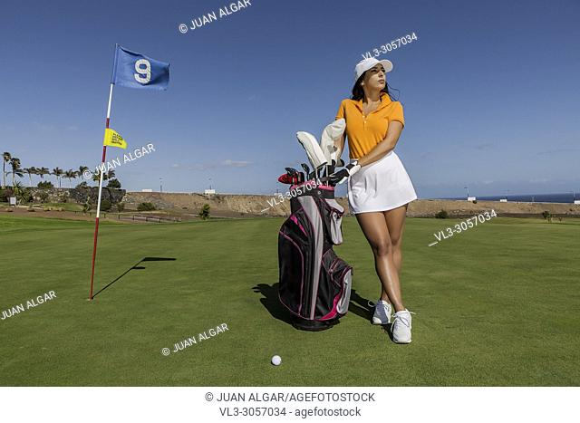 Woman in stylish summer golf outfit standing with bag of drivers on beautiful green course for golf game