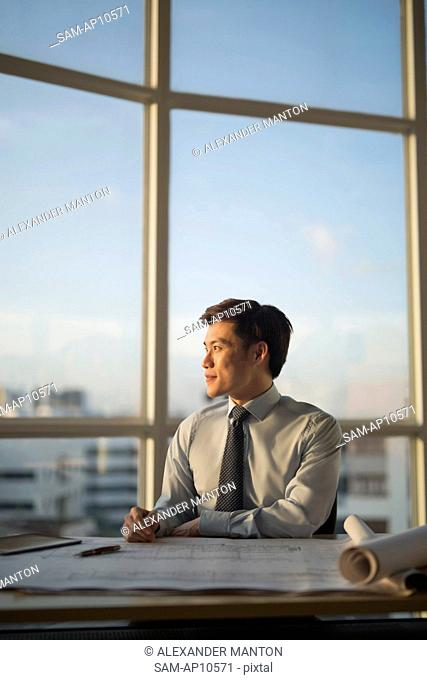 Singapore, Architect with building plans looking out window