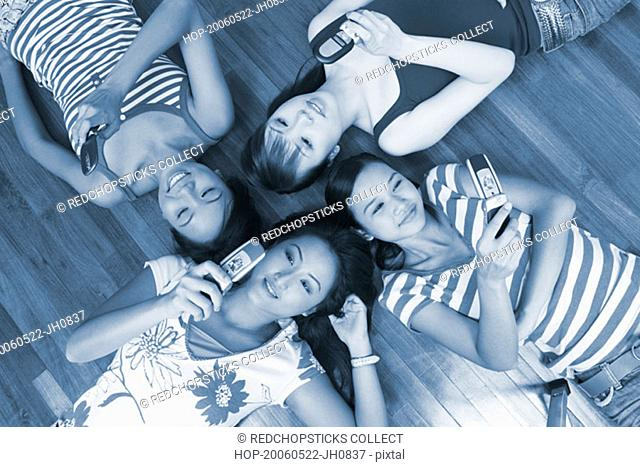 High angle view of four young women lying on a hardwood floor and holding their mobile phones