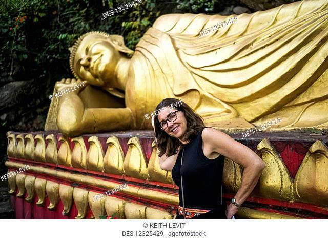 A woman stands beside a large, golden buddhist statue; Luang Prabang, Luang Prabang Province, Laos