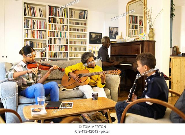 Grandparents and grandchildren playing musical instruments in living room