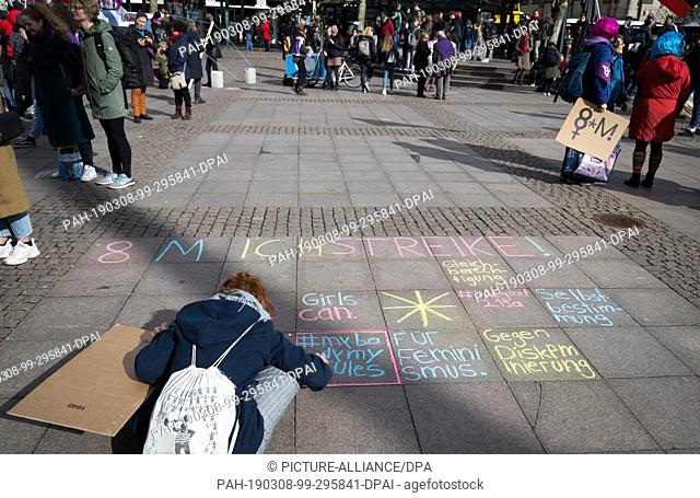 08 March 2019, Hamburg: A young woman writes her protest with chalk on the floor at a demonstration on International Women's Day at the town hall market
