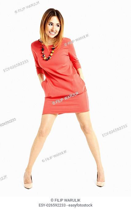 Full length portrait of slim happy woman in a red dress. She bends her body
