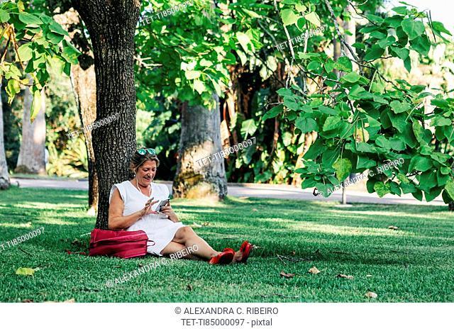 Woman using smart phone under tree
