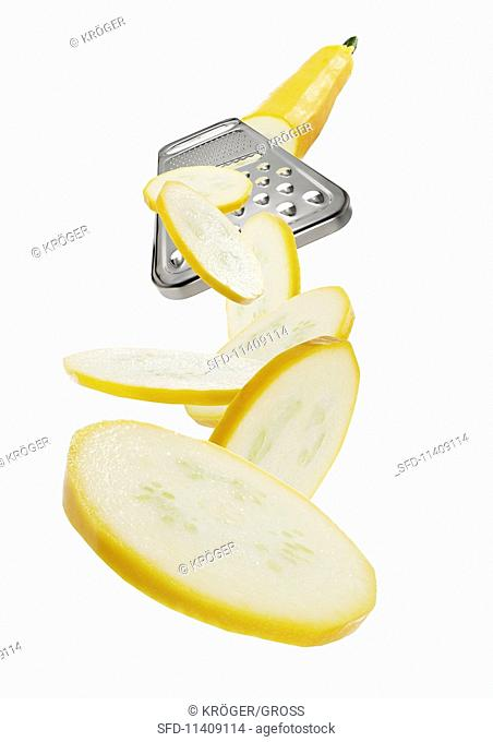 A vegetable grater with a yellow courgette slices
