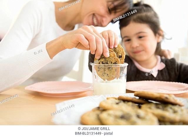 Hispanic mother and daughter dunking cookies in milk