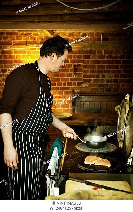 A man in a blue and white striped apron cooking fish on a hot plate on a stove