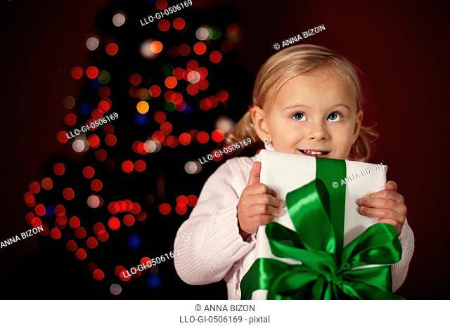 Little girl holding Christmas gift, Debica, Poland