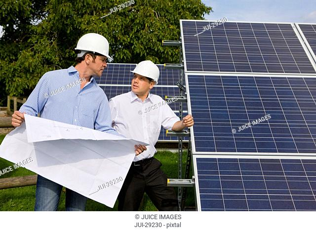 Technicians holding blueprints talking near large solar panels