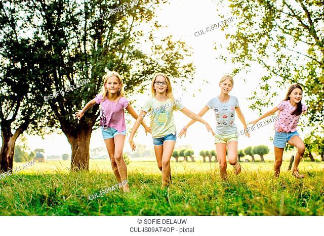Girls running in line, on field, Flanders, Belgium