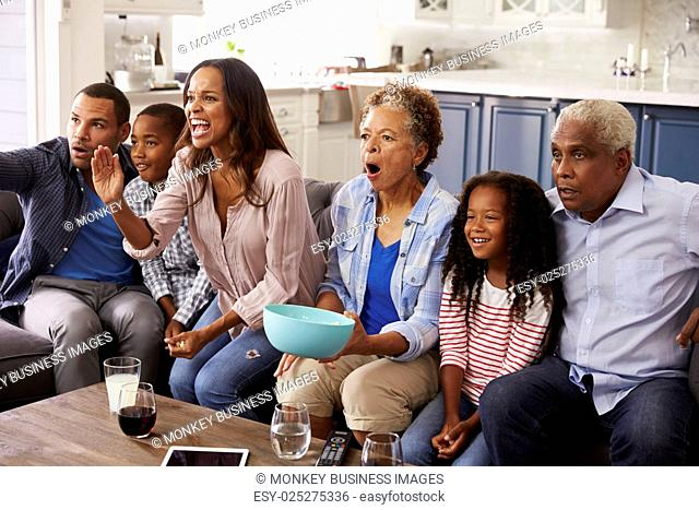 Multi generation black family watching sport on TV at home