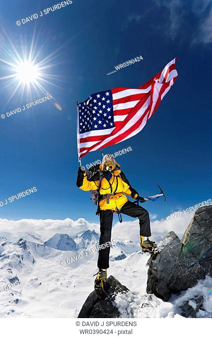 A Mountaineer celebrates by flying the stars and stripes on top of the World