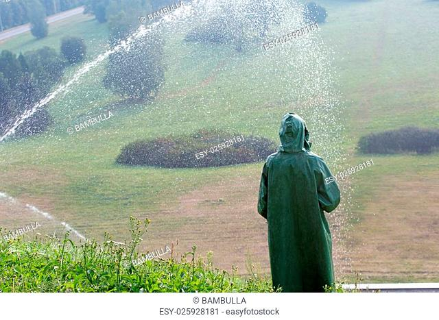 worker during watering green grass lawn with sprinkling tool