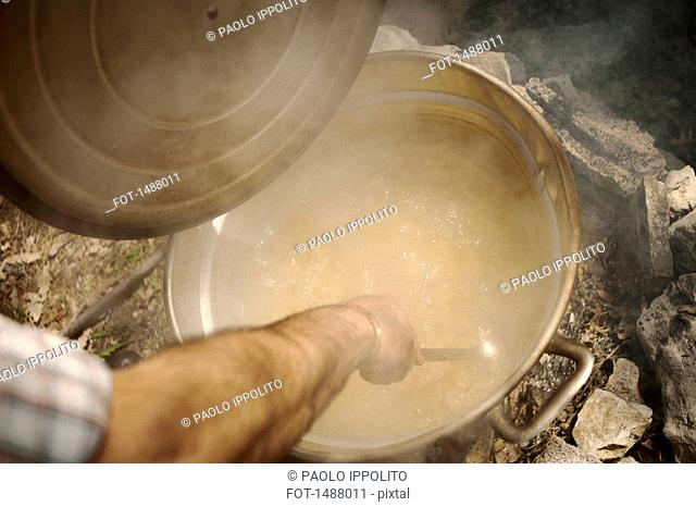 High angle view of man stirring food in pot