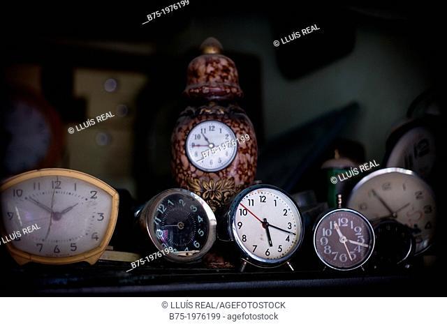 clocks and alarm clocks on a shelf