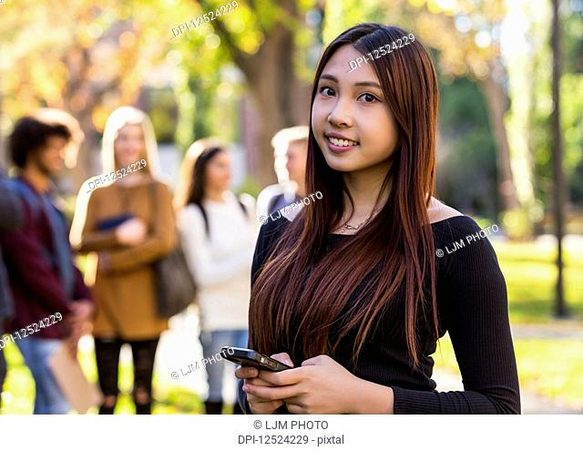 Portrait of a young female International university student holding a smart phone with her friends standing in the background; Edmonton, Alberta, Canada