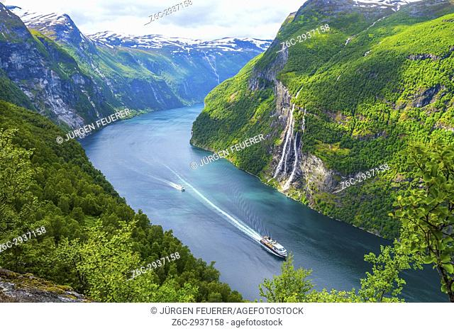 view to the Seven Sisters waterfall and the Geirangerfjorden with a cruise ship of Hurtigruten and a ferry, mountain panorama, Norway