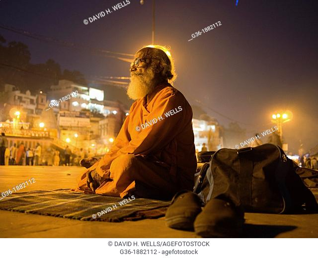 "Pilgrim meditates during ""Arti"" evening prayers on the ghats on the River Ganges in Haridwar in the state of Uttarakhand in northern India"