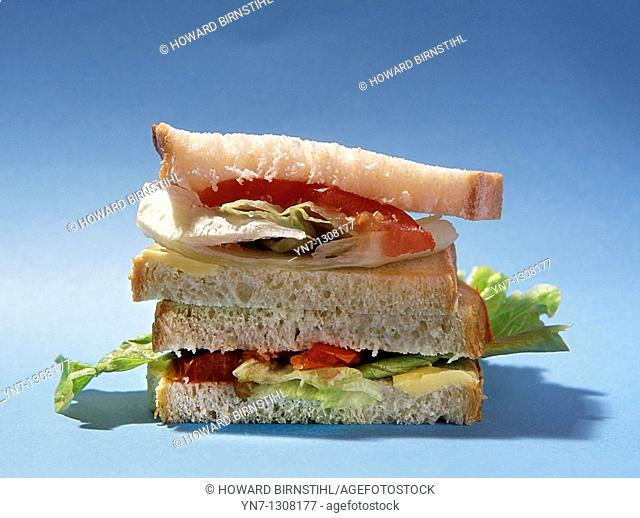 close view of a salad sandwich on a plain blue background