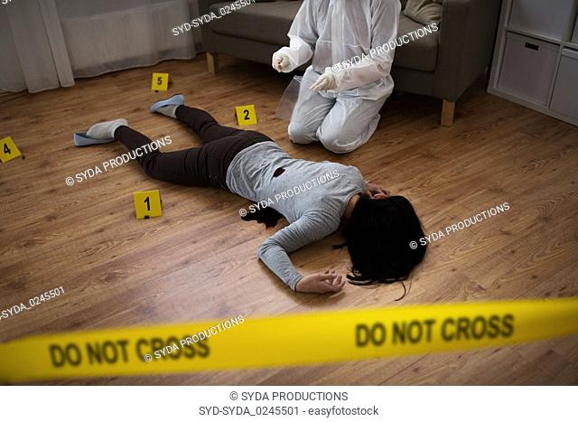 criminalist collecting evidence at crime scene